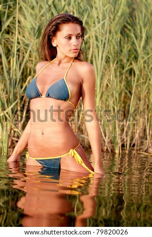 The beautiful bikini model posing against a setting sun on a body of water
