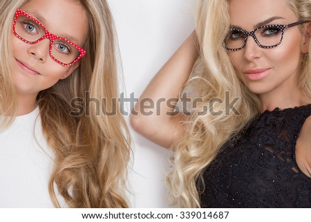 The beautiful blond hair woman mother with green eyes lace blouse a sensual hairstyle with black glasses with daughter girl in a white dress in pink glasses on a white background
