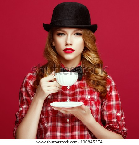 The beautiful blonde in a vintage hat holding a cup of coffee. - stock photo