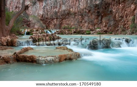 THe beautiful blue waters of Havasu Creek cascading over travertine pools, Grand Canyon, Arizona - stock photo