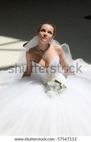 The beautiful bride in wedding dress sits on floor