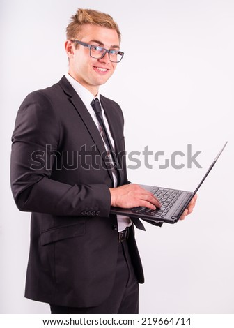 The beautiful businessman working on laptop, on a gray background