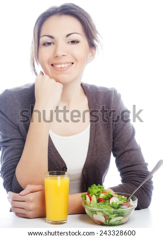 The beautiful cheerful young woman has breakfast salad from fresh vegetables with orange juice - stock photo