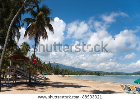 The beautiful coconut palm lined Luquillo Beach located on the large island of Puerto Rico. - stock photo