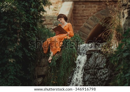 The beautiful countess in a long orange dress sits near a source of water and reading a book, elf, Princess in vintage dress, the queen of the forest,fashionable toning creative computer colors - stock photo