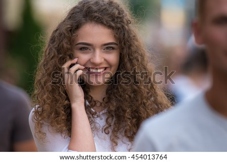 The beautiful curly girl phone with the people stand behind each other - stock photo