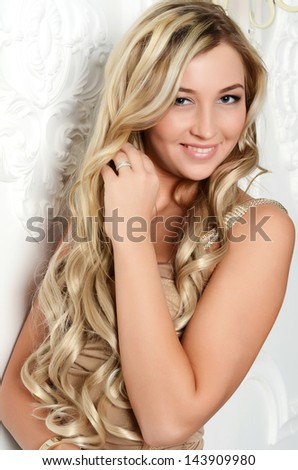 The beautiful elegant woman with long hair at a white wall - stock photo