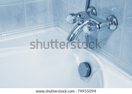 The beautiful faucet and white bath - stock photo