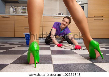 The beautiful female legs standing  against of young man cleaning floor