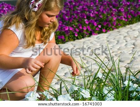 The beautiful girl among flowers - stock photo