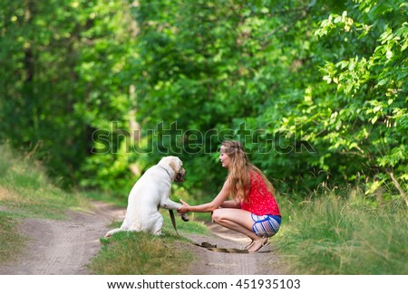 The beautiful girl and dog have sat down on a forest footpath. Dog of breed Labrador.
