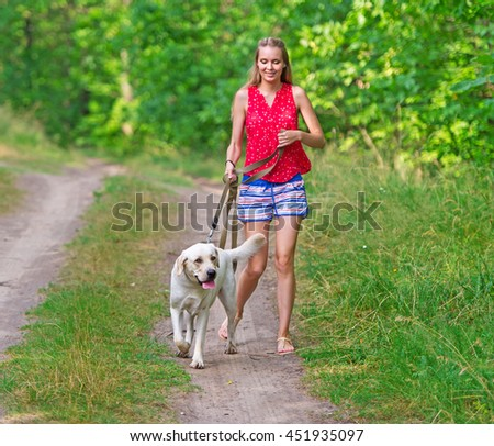 The beautiful girl and dog walk on a forest footpath. Dog of breed Labrador.