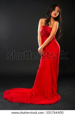 The beautiful girl  asian appearance in a long red dress on black studio background