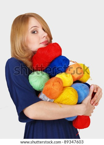 The beautiful girl bears many color hanks of a yarn for knitting