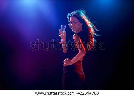 The beautiful girl dancing at the party drinking champagne - stock photo