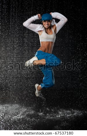 The beautiful girl dancing in water under rain on a black background.  Modern dances. - stock photo