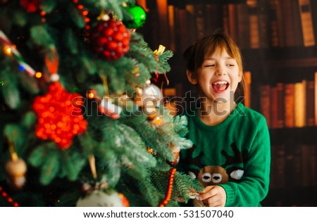 The beautiful girl decorates a Christmas Tree