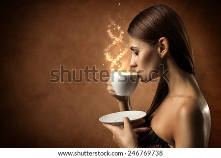 The beautiful girl drinks coffee. The magic inscription flies out from a cup - stock photo