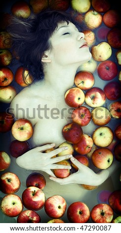 The beautiful girl floating in apples photo - stock photo
