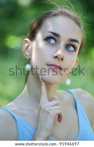 The beautiful girl holds a finger at the person and thoughtfully looks upwards