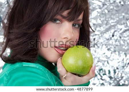 The beautiful girl holds a ripe apple