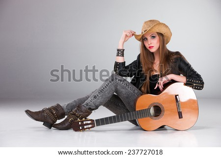 The beautiful girl in a cowboy's hat  and acoustic guitar on a gray background - stock photo