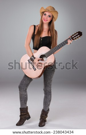 The beautiful girl in a cowboy's hat playing acoustic guitar on a gray background. Portrait in full growth - stock photo
