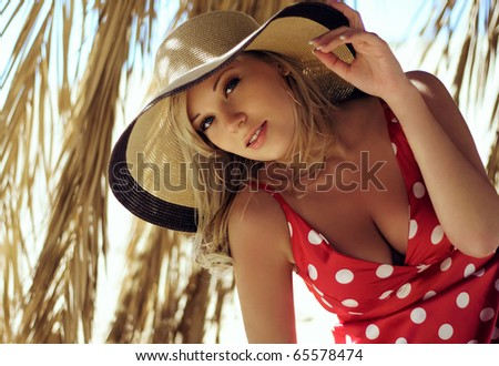 The beautiful girl in a hat on a beach - stock photo