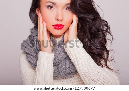 the beautiful girl in a scarf and a warm sweater with red lips
