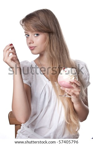 The beautiful girl in a white dress with wild strawberry and a dessert in hands