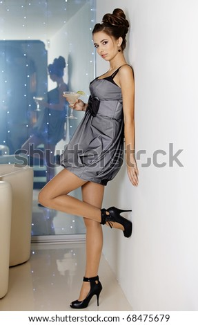 The beautiful girl in an evening dress has a rest on a party