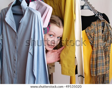 The beautiful girl in clothes shop looks out among jackets and jumpers