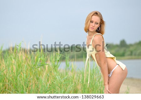 The beautiful girl in the torn undershirt on a beach