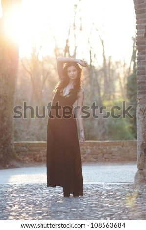 the beautiful girl in the woods thinks lit by the sunset - stock photo