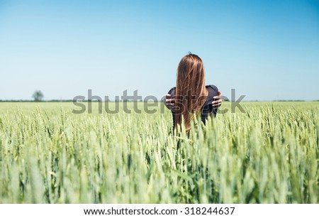The beautiful girl is on a wheaten field