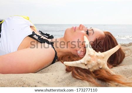 The beautiful girl lies on sea coast with shells nature vacation woman outdoor - stock photo