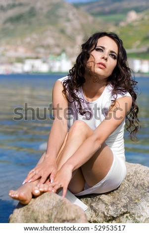 The beautiful girl sits on a rock near the sea