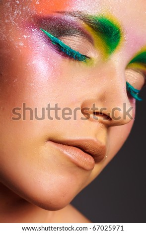 The beautiful girl with a creative make-up on face - stock photo