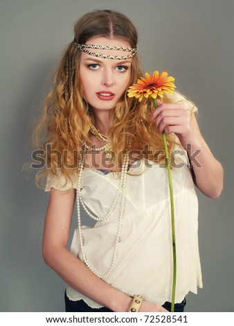 The beautiful girl with a long fair hair in a white blouse and with a flower in her hands - stock photo
