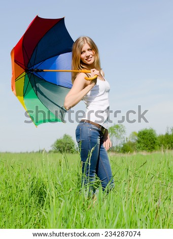The beautiful girl with a multi-coloured umbrella - stock photo