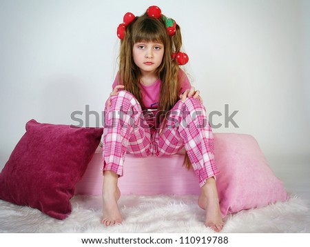 The beautiful girl with hair curlers sits on pillows - stock photo
