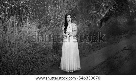 The beautiful girl with long black hair and in a white dress stands on the dusty country road. The young brunette near high dry grass