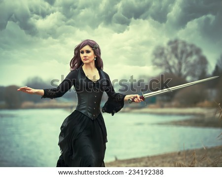 The beautiful gothic girl holds a sword in a hand - stock photo