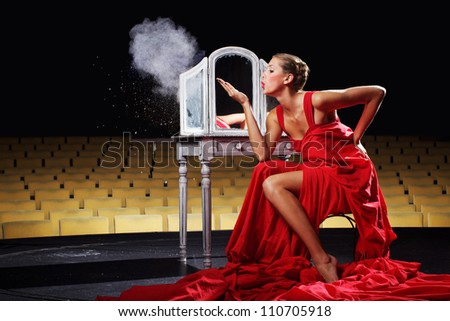 The beautiful lady in red on the theater stage - stock photo