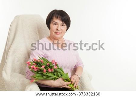 the beautiful mature woman sits on a chair with a bouquet of tulips - stock photo