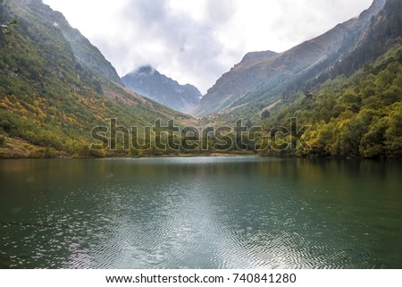 The beautiful mountain lake in the picturesque gorge, the cloudy sky