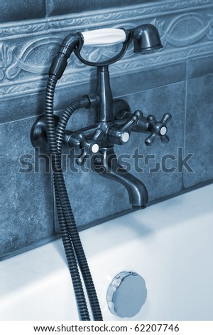 The beautiful old faucet in a bathroom - stock photo