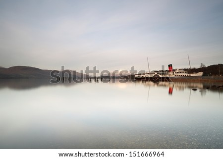 The beautiful paddle steamer 'PS Maid of the Loch' by the shores of Loch Lomond with a snow-capped Ben Lomond in the background - stock photo