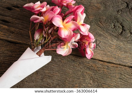 The beautiful pink Plumeria flower on the old wood background still life