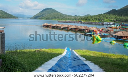 The beautiful place with housing raft in modern style in dam, blue clear sky, and mountain. the reflection on the surface of water in dam